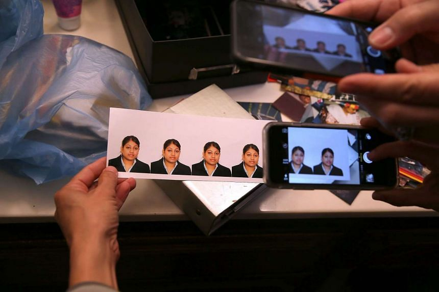 Reporters take pictures of photographs found inside the home of shooting suspect Syed Farook.
