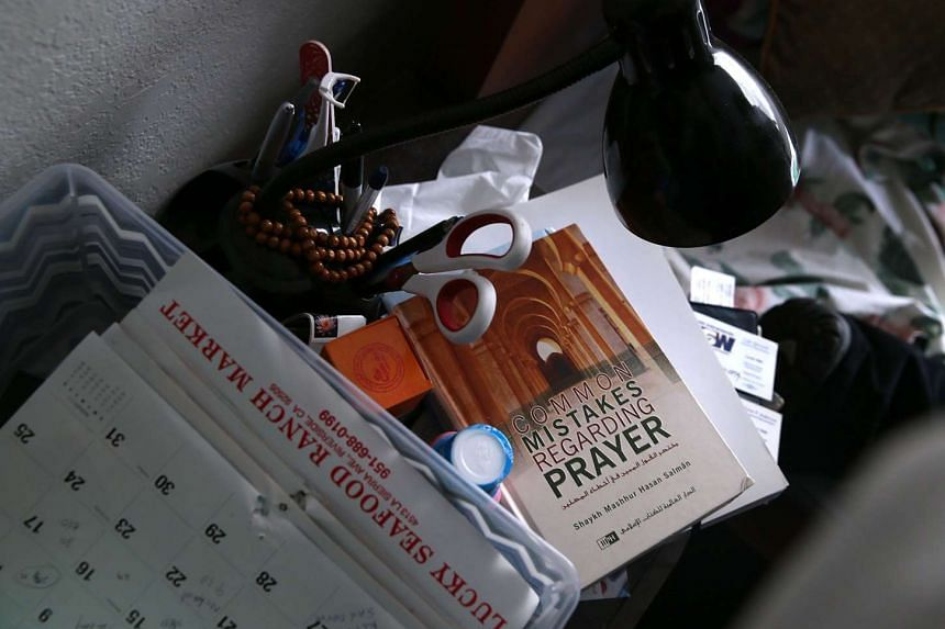 A book about prayer sits on a bedside table.