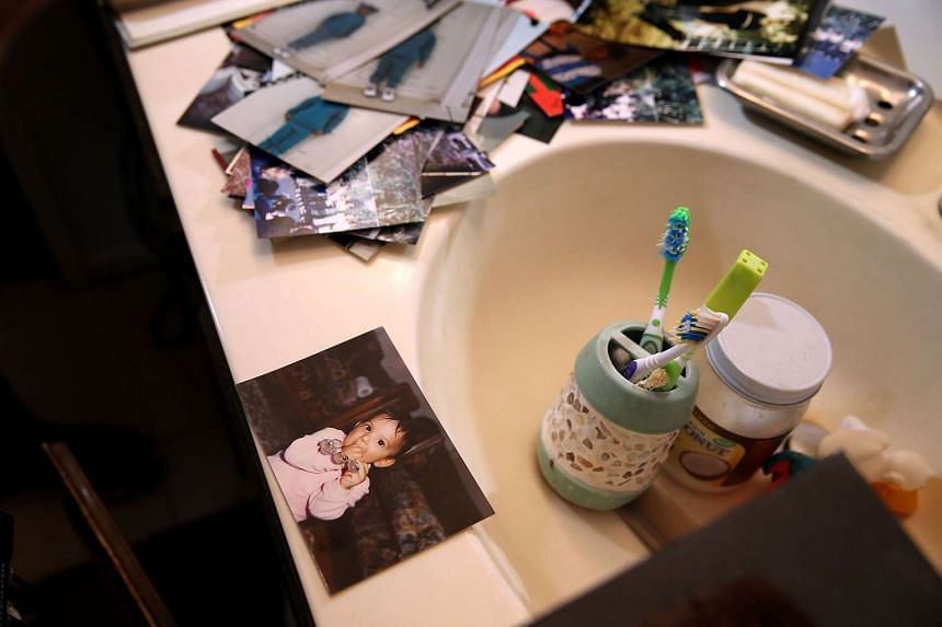 Photographs sit on the bathroom sink.