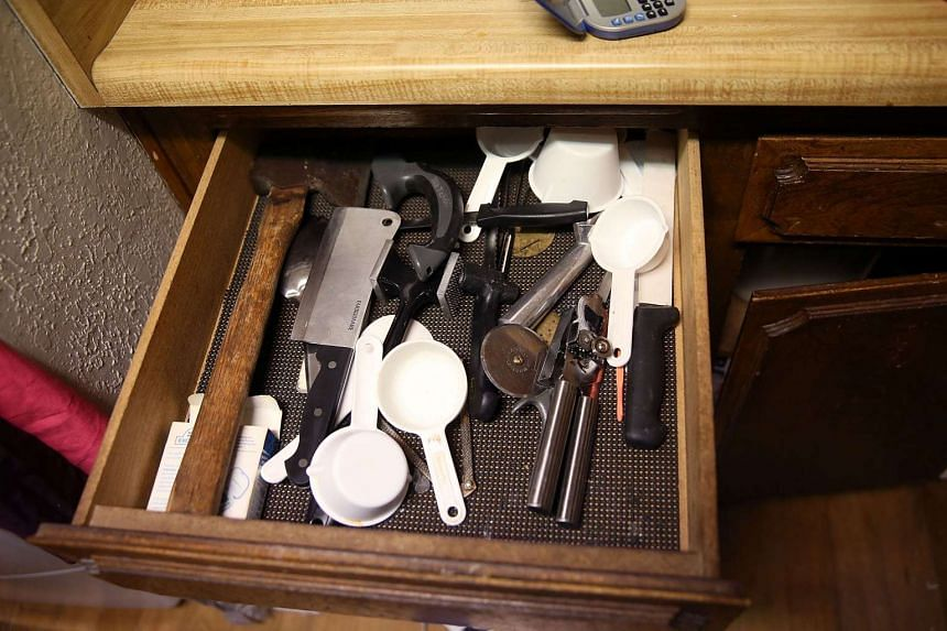 A hatchet sits in a kitchen drawer.
