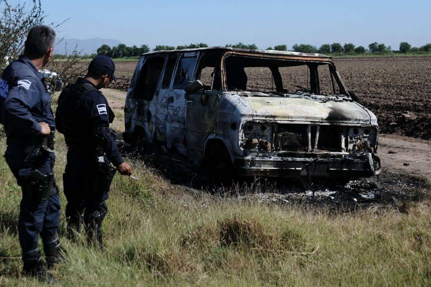Policemen standing by the burnt van in which the two Australians were said to be travelling in, on Nov 21.