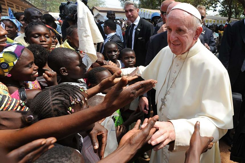 Pope Francis (right) greets children during a visit to a refugee camp in Bangui.