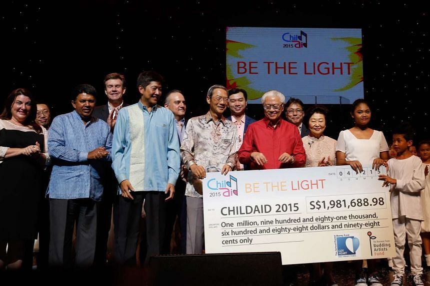 Below: Singapore Press Holdings (SPH) chairman Lee Boon Yang (centre) presenting a cheque for the money raised to two ChildAid performers - Sri Dhea Dhanira Mohd Riszuan, 10, and Nur Adrianz Kamaruddin, nine - in the presence of the guest of honour,