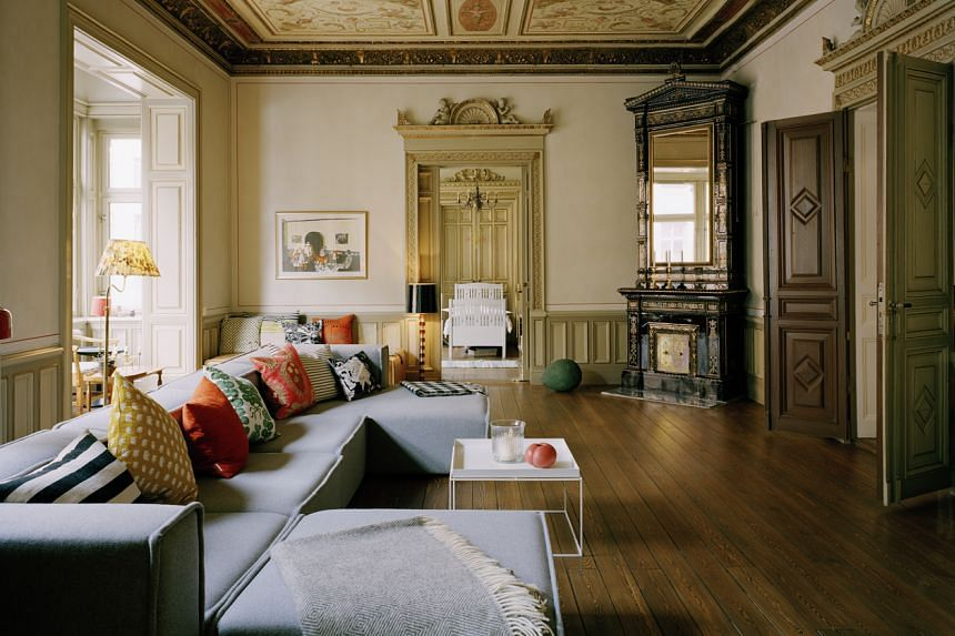 The living room of an apartment in Strahattfabriken in Stockholm, Sweden, has restored floorboards and a handpainted ceiling. A family of six, including four children, live here. The building was a former hat factory.