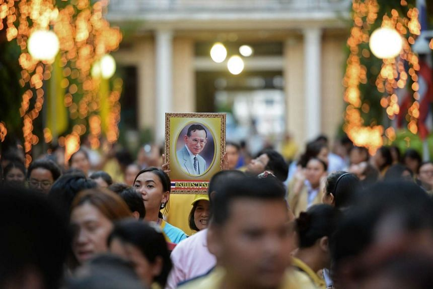 A Thai well-wisher holding a portrait of King Bhumibol Adulyadej at the Siriraj hospital in Bangkok, where the King has been staying for months, on Dec 4, the eve of his 88th birthday.