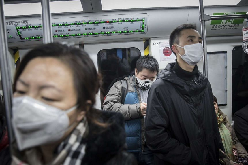 Commuters wear face masks while riding in the subway in Beijing, China, on Dec 1, 2015.
