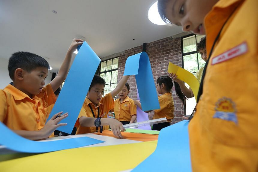 Primary 3 students from Yumin Primary School work on creating a self-made book at the workshop room in Playeum.