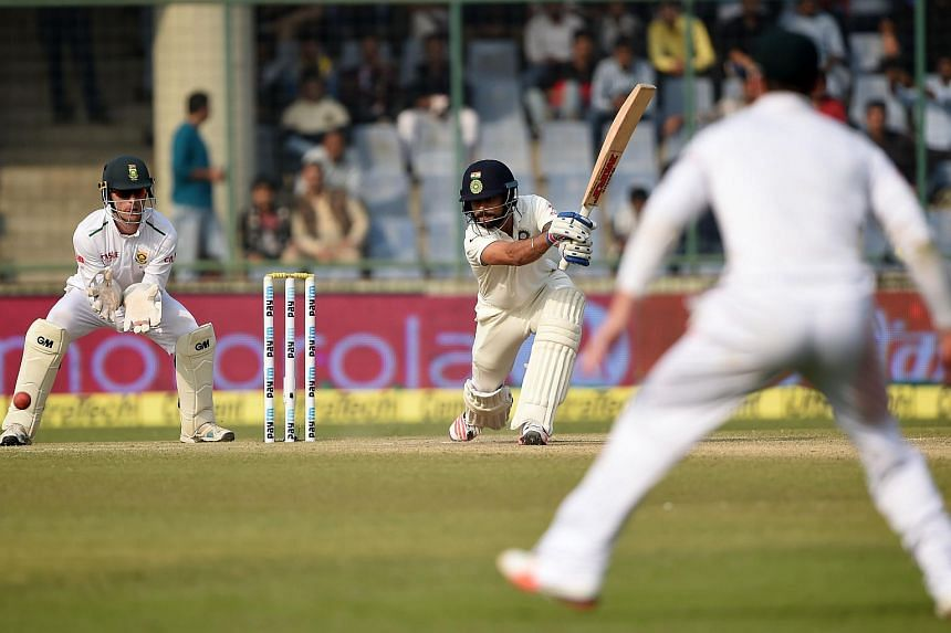 India's captain Virat Kohli (centre) plays a shot as South Africa's wicketkeeper Dane Vilas (left) looks on during the third day of the fourth Test cricket match between India and South Africa.