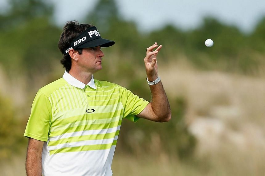Bubba Watson of the United States reaches for his golf ball on the first green during the third round of the Hero World Challenge.