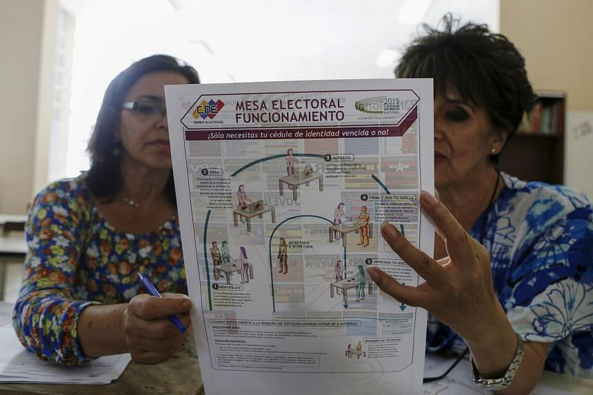Electoral workers read a brochure which explains the voting process in a school, which will function as a polling station in Caracas, Dec 5, 2015.