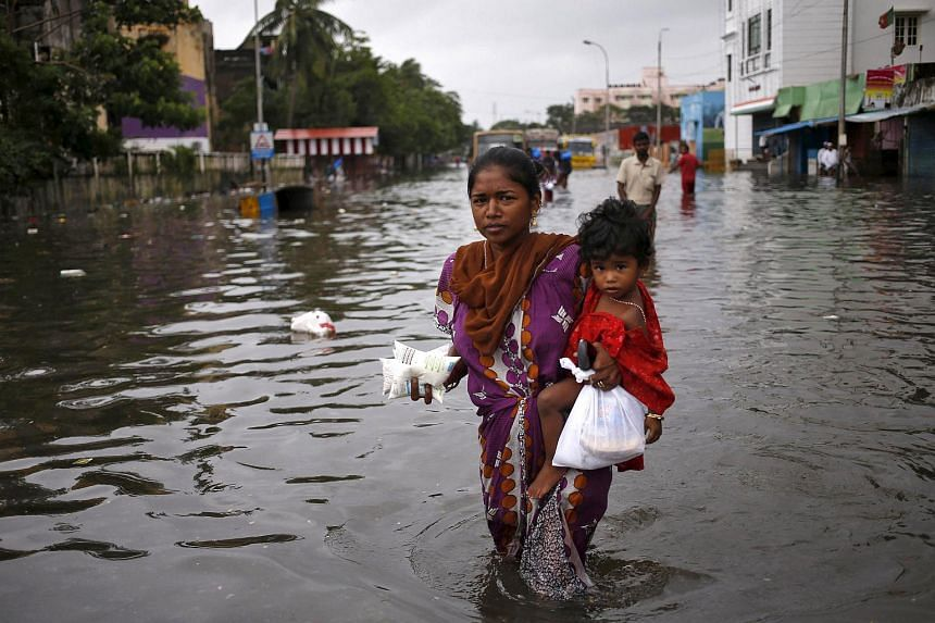 A woman carries her child and milk packets as she wades through a flooded street in Chennai, India, on Dec 5, 2015.