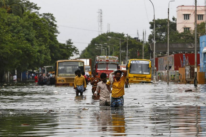 People wade through a flooded road in Chennai, India, on Dec 5, 2015.