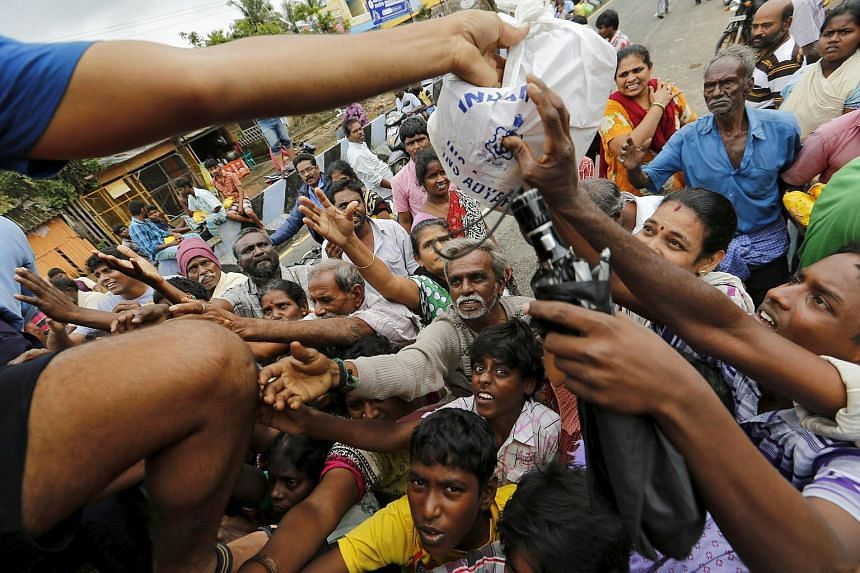 Flood-affected people raise their hands to receive free food being distributed by Indian Navy personnel in Chennai, India, on Dec 5, 2015.