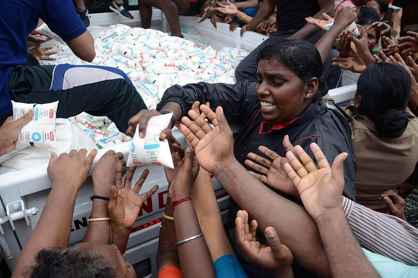 Indian volunteers distribute packets of milk to flood affected residents in Chennai on Dec 5, 2015.