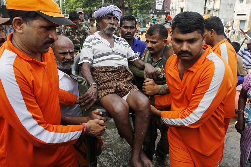 National Disaster Response Force personnel carry an elderly man rescued from floodwaters in Chennai, India, on Dec 4, 2015.