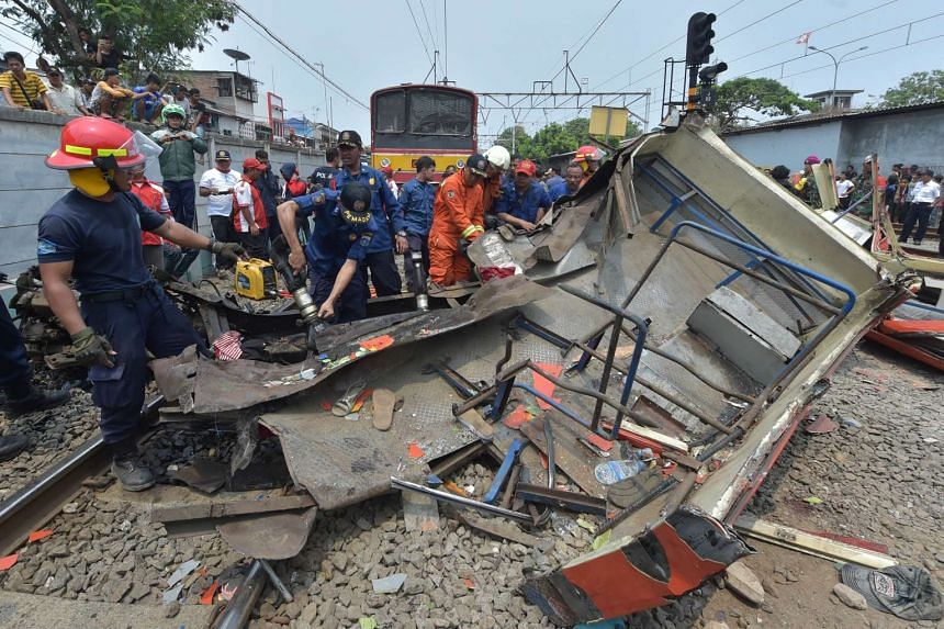 Indonesian firefighters cut the wreckage of a minibus after it collided with a train in Jakarta on Dec 6, 2015.