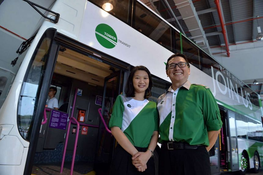 Tower Transit employees Nichelle Pang and Thng Kim Seng (right) posing with the new bus captain's uniform.