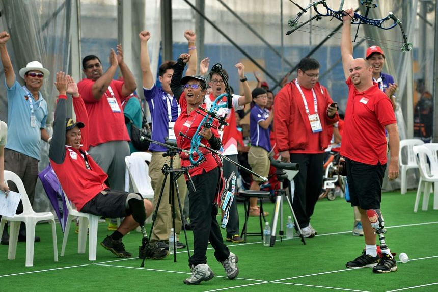 Singapore archer Syahidah Alim (centre) and teammate Robert Fuchs celebrating after they won the Archery Mixed Team Compound gold on Dec 6, 2015.