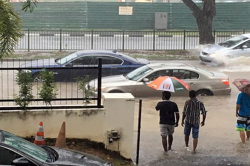 Cars stranded in floodwaters along Yio Chu Kang Road, just outside the Church of St Vincent de Paul. Yesterday's downpours pushed water levels in drains and canals close to the brink, with flooding reported in areas such as Ang Mo Kio, Buangkok, Houg