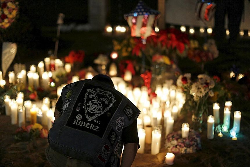 Investigators searching the home of Syed Farook and his wife Tashfeen Malik unearthed a cache of weapons. A young boy kneeling in front of a pop-up memorial in San Bernardino, California, on Friday, following Wednesday's attack where 14 people were g
