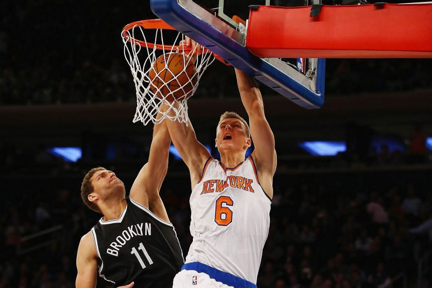 Kristaps Porzingis (No. 6) has no hesitation going for a dunk even as Brooklyn Nets' Brook Lopez tries to block his effort.