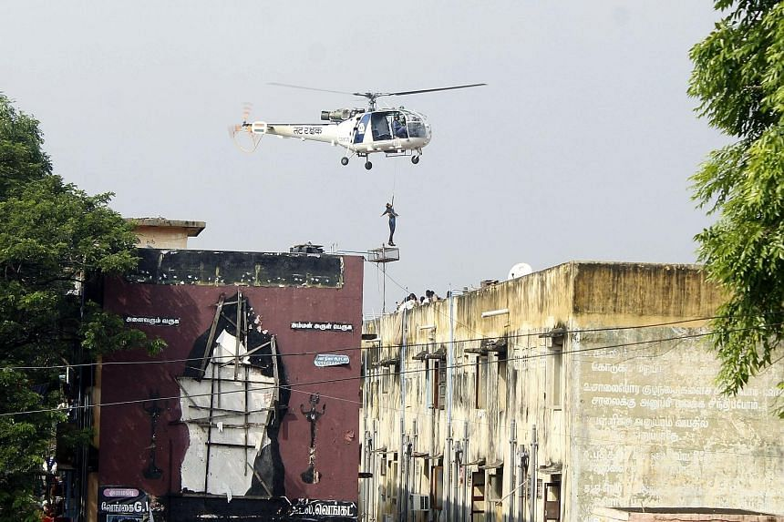 An Indian rescue helicopter lifting a man off a roof of apartment buildings surrounded by floodwaters in Chennai on Friday. Thousands of rescuers are racing to evacuate victims of flooding in Tamil Nadu.