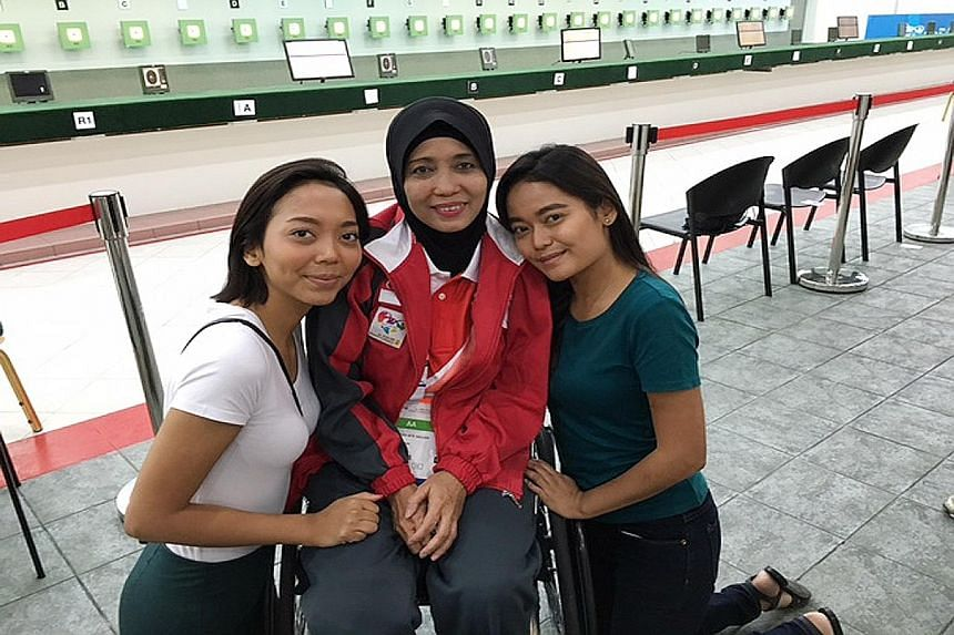 Dhamirah (in white) and Farhana with their mother Faridah, who is competing in shooting at the Asean Para Games, after pursuing the sport for only nine months.