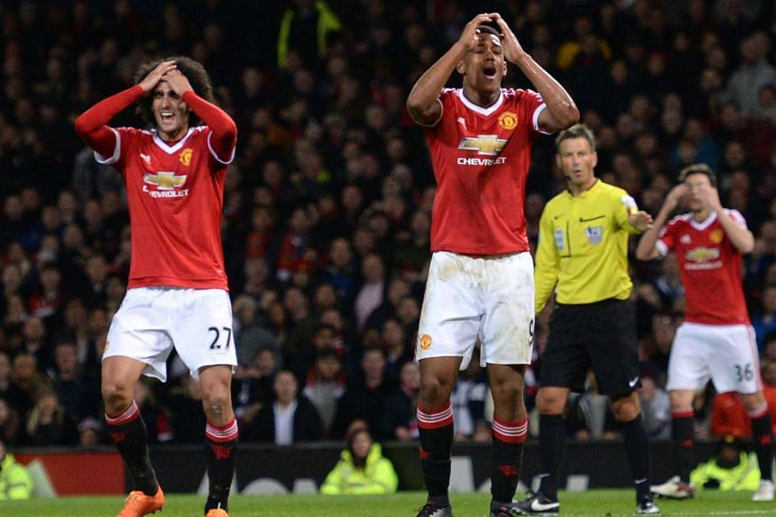 Manchester United striker Anthony Martial (centre) reacts after missing a goal scoring opportunity.