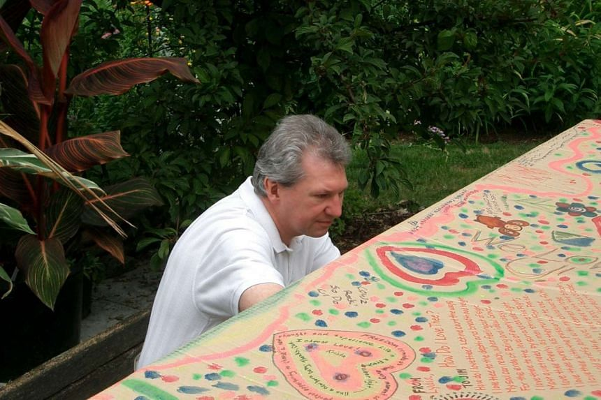 Mr George Barrett decorating his father's fibreboard casket. Mr Barrett and his wife Char are among a growing number of Americans who are choosing home funerals for their loved ones.