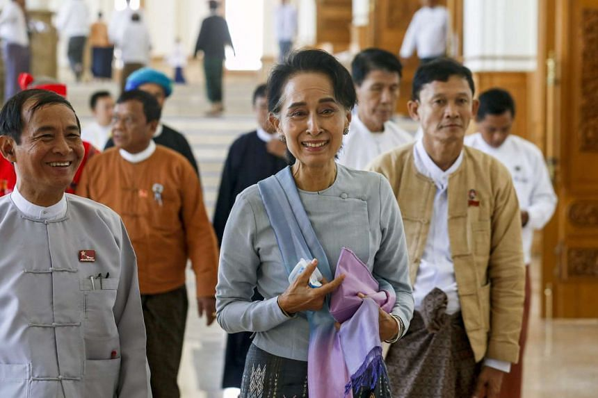 Suu Kyi (centre) accompanied by her party members during a break in the parliament session.