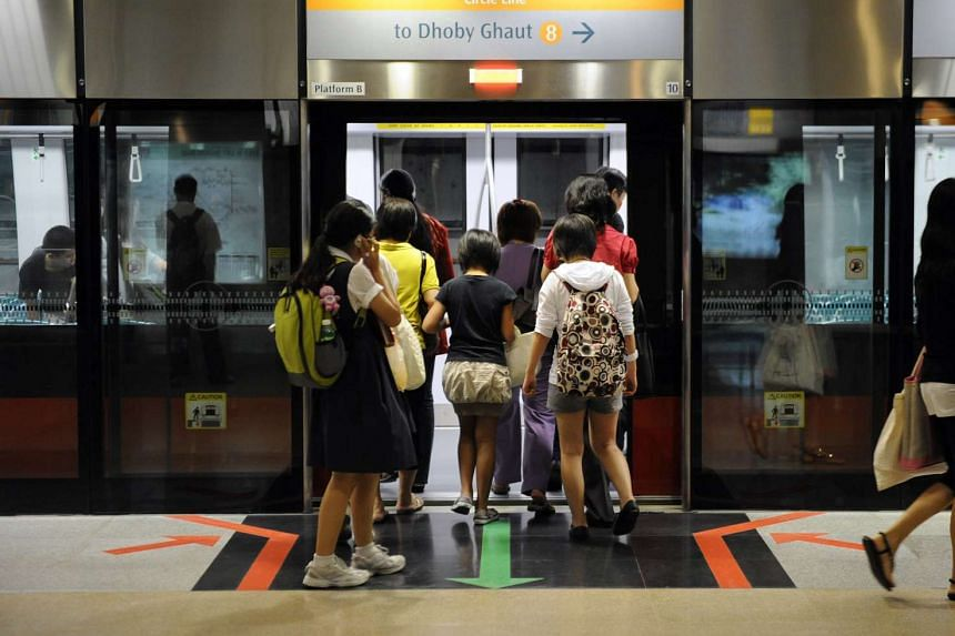 Passengers board a train on the Circle Line at Bishan station.