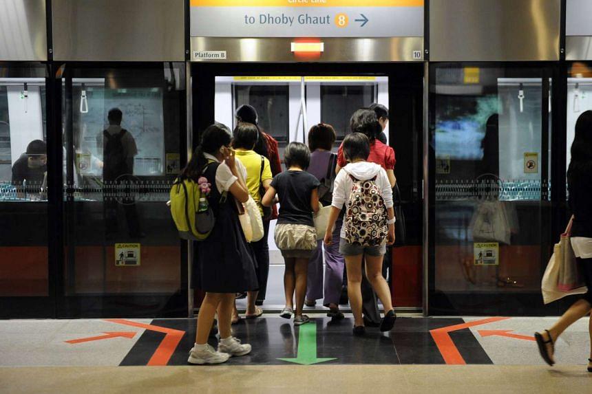 Passengers board a train on the Circle Line at Bishan station.