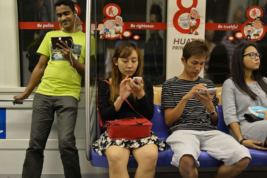 Commuters on the MRT using their mobile devices.