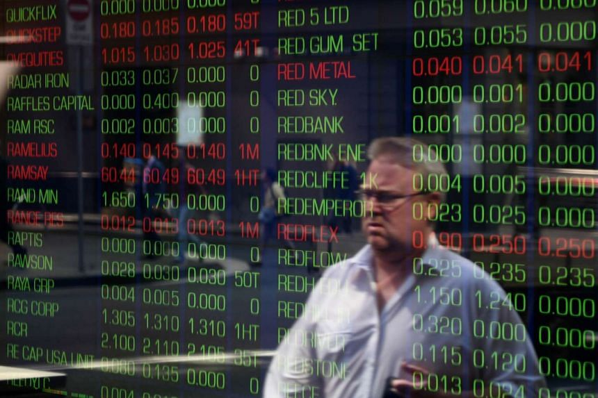 A passerby is reflected in the window of the Sydney Stock Exchange showing the benchmark S&P/ASX200 index in Sydney on Sept 18, 2015.