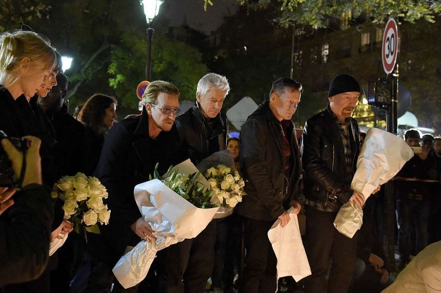 Irish band U2 (from left) lead singer Bono, bass player Adam Clayton, drummer Larry Mullen Jr and guitarist The Edge pay homage to attacks' victims near the Bataclan concert hall on Nov 14, 2015 in Paris, a day after a series of coordinated attacks i