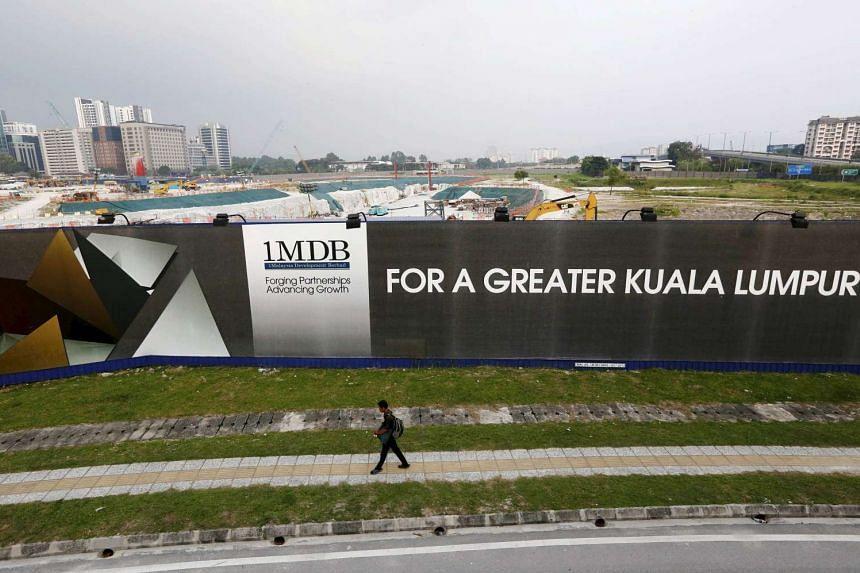 A man walks past a 1MDB billboard at the funds flagship Tun Razak Exchange development in Kuala Lumpur, in this Mar 1, 2015 file photo.