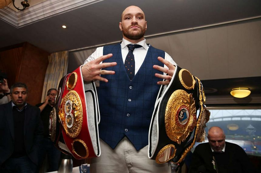 Tyson Fury poses with his belts after a press conference.