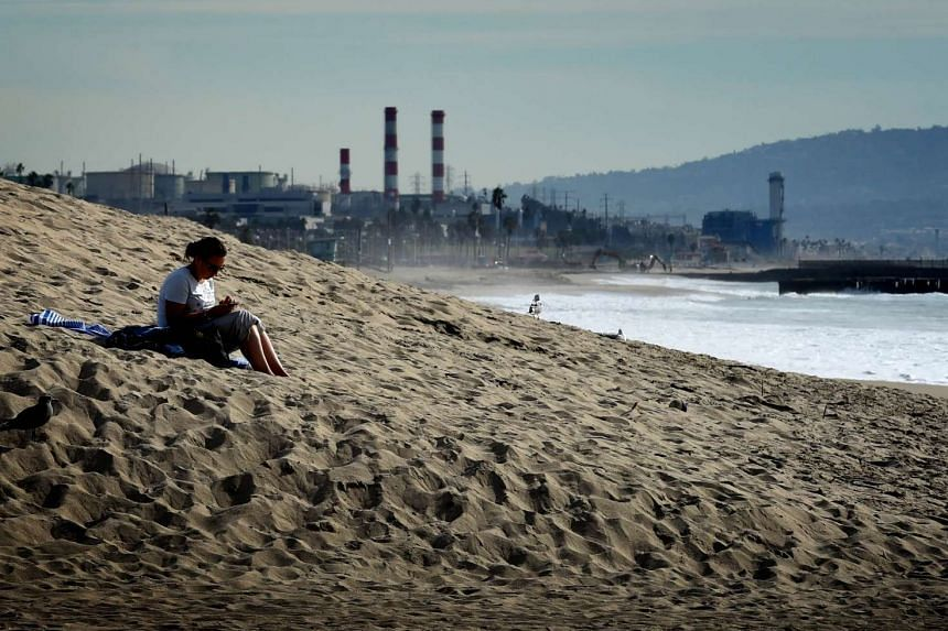 A woman sits on a sand berm created by city workers to protect houses from El Nino storms and high tides at Playa Del Rey beach in Los Angeles, California on Nov 30, 2015.