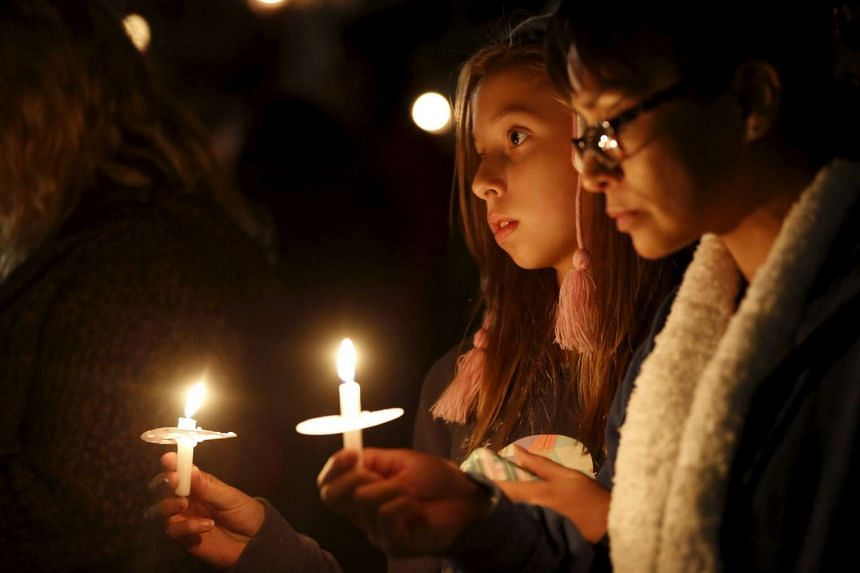 Attendees reflect on the tragedy of the Dec 2, 2015, attack during a candlelight vigil in San Bernardino, California on Dec 3, 2015. California shooter Syed Rizwan Farook, 28, and his wife Tashfeen Malik, 27, were killed in a shootout with police.