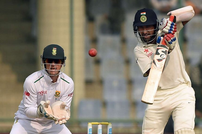 India's Cheteshwar Pujara (right) is watched by South Africa's wicketkeeper Dane Vilas at the Feroz Shah Kotla stadium in New Delhi on Dec 5, 2015.