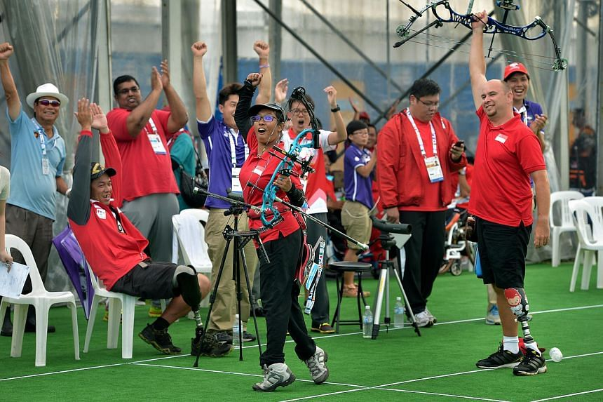Singapore's Syahidah Alim (centre) and her teammate, Robert Fuchs (right) celebrate with the Singapore team after winning gold at the Archery Mixed Team Compound event.