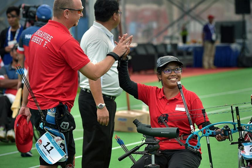 Singapore's Syahidah Alim (right) celebrates with her teammate, Robert Fuchs (left) after winning gold at the Archery Mixed Team Compound event.
