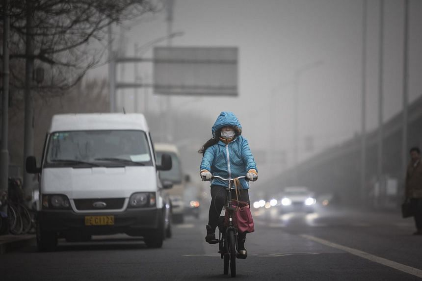 A woman wearing a face mask rides a bicycle along a street in Beijing, China, on Dec 1, 2015.