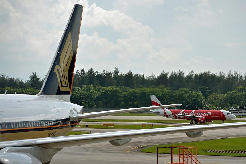 A Singapore Airlines plane and an Air Asia plane at Changi Airport Terminal 2 runway.