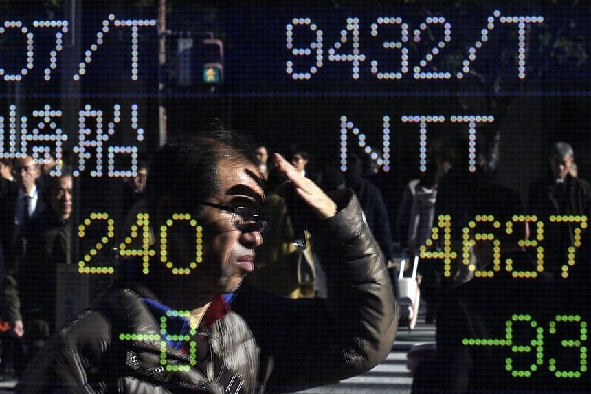 A pedestrian is reflected in a stock market indicator board in Tokyo, Japan, on Dec 4, 2015.