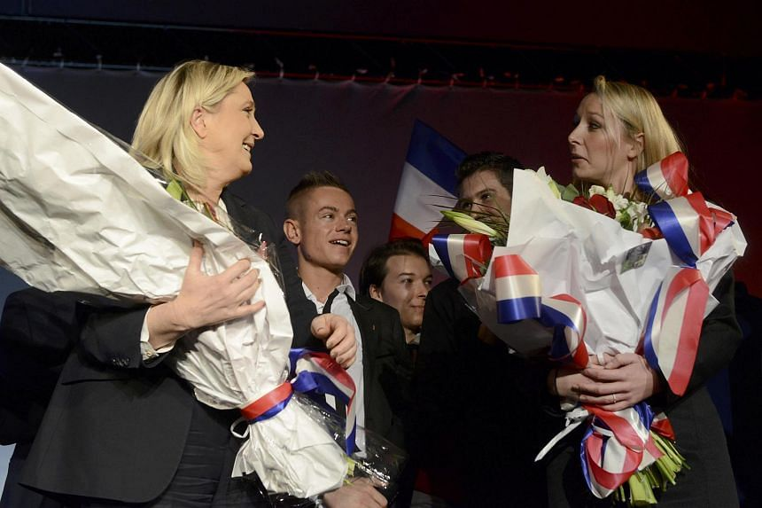 Marine Le Pen (left) and Marion Marechal-Le Pen react on stage with flowers at the end of a political rally.