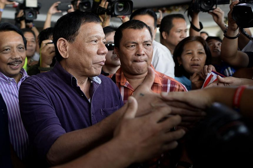 Davao mayor Rodrigo Duterte (front left) shakes hands with supporters outside a hotel in Manila on Nov 30, 2015.