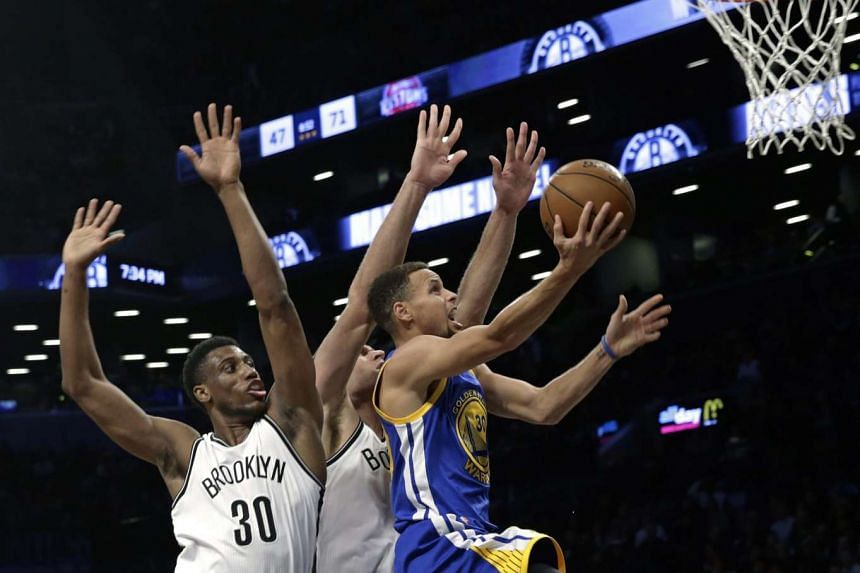 Golden State Warriors guard Stephen Curry drives past Brook Lopez (centre) and Thaddeus Young (left) for a layup at the Barclays Centre in Brooklyn on Dec 6, 2015.