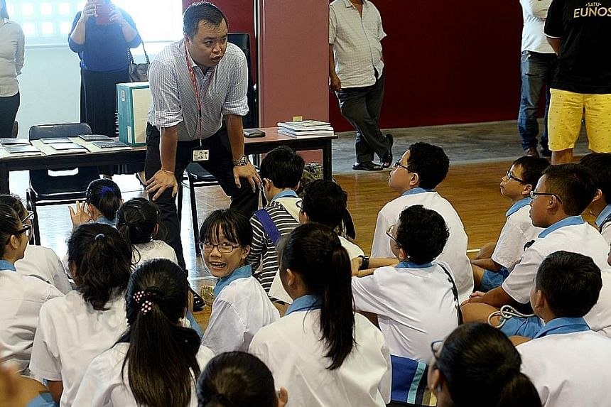 A teacher speaks to pupils before the PSLE results are handed out. Some parents set the bar too high and end up reacting badly when their children fail to meet their lofty expectations.