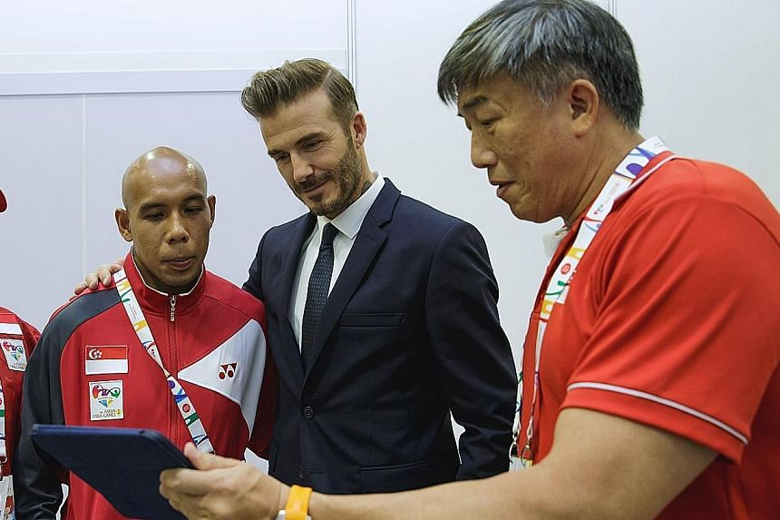 Football icon David Beckham and cerebral palsy footballer Khairul Anwar Kasmani watching as Sport Singapore chief executive Lim Teck Yin showed them highlights of the Singaporean's long-range stunners made during the ongoing Asean Para Games. Athlete